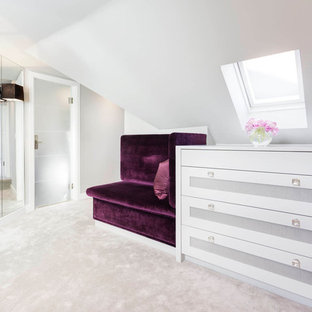 Large contemporary dressing room for women in London with shaker cabinets, white cabinets and carpet.