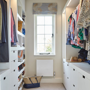 This is an example of a medium sized contemporary gender neutral walk-in wardrobe in London with flat-panel cabinets, white cabinets, carpet and beige floors.