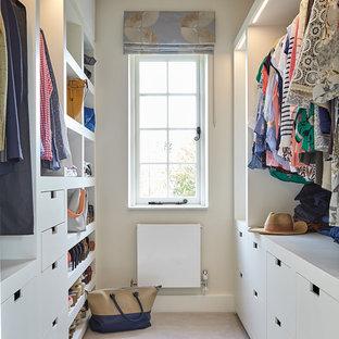 ロンドンの中くらいの男女兼用コンテンポラリースタイルのおしゃれなウォークインクローゼット (フラットパネル扉のキャビネット、白いキャビネット、カーペット敷き、ベージュの床) の写真