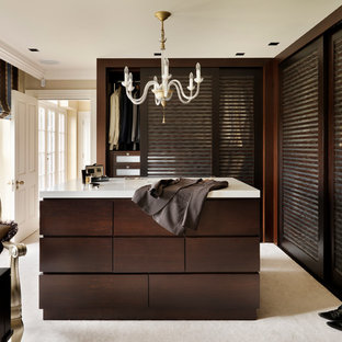 Large classic dressing room for men in London with dark wood cabinets and carpet.