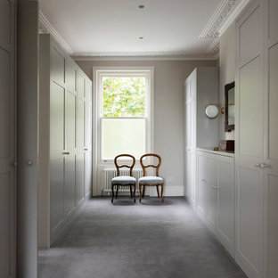 This is an example of a large contemporary gender neutral wardrobe in London with raised-panel cabinets, grey cabinets, carpet and grey floors.