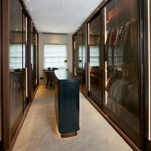 Idee per un grande spazio per vestirsi unisex minimal con ante di vetro, ante marroni, moquette e pavimento beige