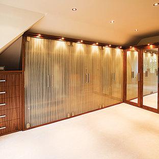 Foto de armario vestidor unisex, ecléctico, de tamaño medio, con armarios tipo vitrina, puertas de armario de madera oscura, moqueta y suelo beige