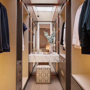 Design ideas for a medium sized contemporary gender neutral dressing room in London with brown cabinets, light hardwood flooring and open cabinets.