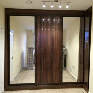 Immagine di un armadio o armadio a muro unisex contemporaneo di medie dimensioni con ante di vetro, ante in legno bruno e parquet chiaro