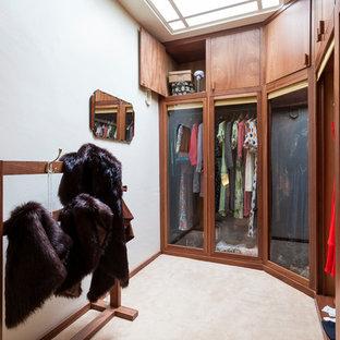 Foto di uno spazio per vestirsi unisex vittoriano con ante di vetro, ante in legno scuro e moquette