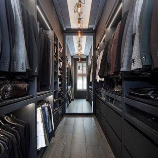 Modelo de armario y vestidor de hombre, urbano, de tamaño medio, con armarios con paneles lisos, puertas de armario negras, suelo de madera oscura y suelo marrón