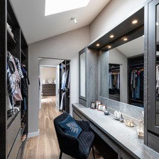 Diseño de vestidor de mujer, clásico renovado, de tamaño medio, con armarios con paneles lisos, puertas de armario de madera en tonos medios, suelo de madera clara y suelo marrón
