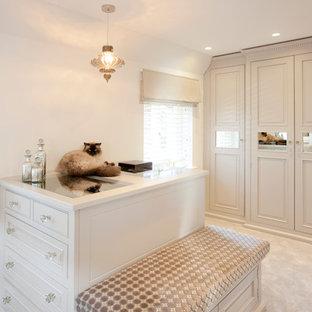 ハンプシャーのトラディショナルスタイルのおしゃれなウォークインクローゼット (インセット扉のキャビネット、ベージュのキャビネット、カーペット敷き) の写真