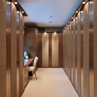 Photo of a large contemporary walk-in wardrobe in Cambridgeshire with carpet, dark wood cabinets, flat-panel cabinets and beige floors.