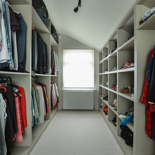 Inspiration for a medium sized contemporary gender neutral walk-in wardrobe in London with open cabinets, carpet and beige floors.