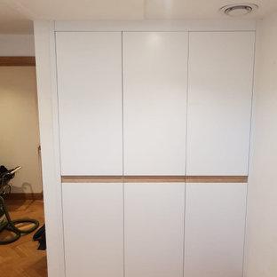 エセックスの中くらいの男女兼用モダンスタイルのおしゃれな壁面クローゼット (インセット扉のキャビネット、白いキャビネット) の写真