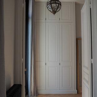Exemple d'un dressing room tendance neutre avec des portes de placard blanches, un sol en bois clair et un placard avec porte à panneau surélevé.