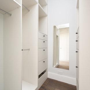 Diseño de armario y vestidor unisex, actual, pequeño, con armarios con paneles lisos, puertas de armario grises y suelo marrón