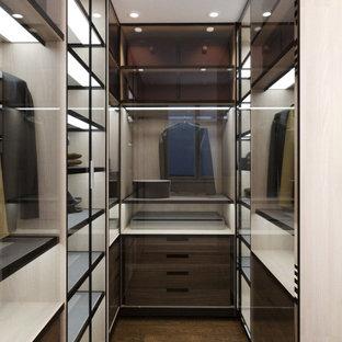Cette photo montre un petit dressing moderne neutre avec un placard à porte vitrée et des portes de placard en bois sombre.