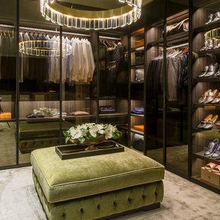 Foto di uno spazio per vestirsi unisex contemporaneo con ante di vetro, ante nere, moquette e pavimento beige
