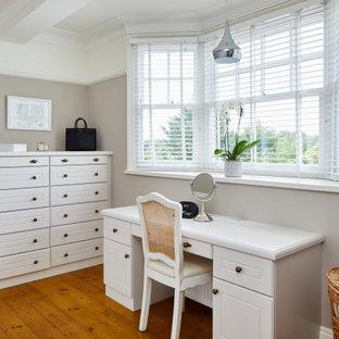 Ejemplo de vestidor unisex, tradicional, de tamaño medio, con armarios con puertas mallorquinas, puertas de armario blancas, suelo de madera en tonos medios y suelo marrón