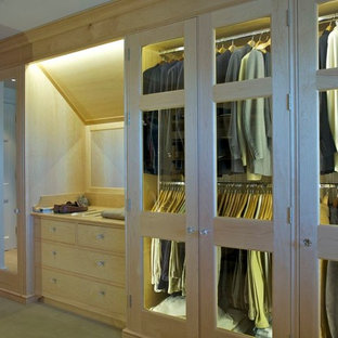 Inspiration for a medium sized modern walk-in wardrobe for men in London with glass-front cabinets, light wood cabinets and carpet.