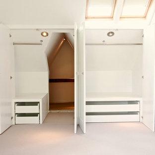 На фото: гардеробная комната среднего размера, унисекс в современном стиле с белыми фасадами и ковровым покрытием с