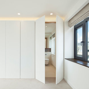 Minimalist gender-neutral carpeted walk-in closet photo in London with white cabinets and flat-panel cabinets