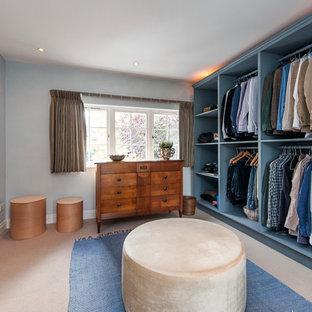ロンドンの男性用トランジショナルスタイルのおしゃれなフィッティングルーム (オープンシェルフ、青いキャビネット、カーペット敷き、ベージュの床) の写真
