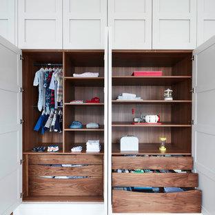 Idée de décoration pour un grand placard dressing tradition neutre avec un sol en bois brun, un placard avec porte à panneau encastré, des portes de placard grises et un sol beige.