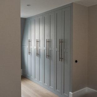 Foto di una cabina armadio minimal con ante in stile shaker, ante blu e parquet chiaro
