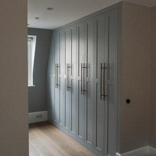 Foto di una cabina armadio contemporanea con ante in stile shaker, ante blu e pavimento in legno massello medio
