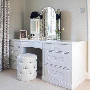Diseño de vestidor de mujer, clásico, de tamaño medio, con armarios estilo shaker, puertas de armario blancas, moqueta y suelo blanco