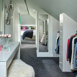 Design ideas for a contemporary dressing room for women in London with flat-panel cabinets, grey cabinets, carpet and grey floors.