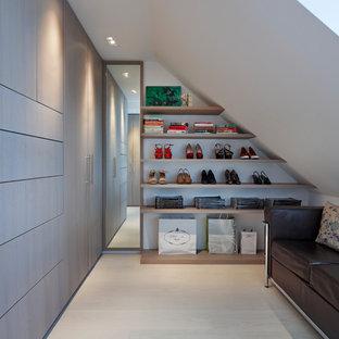 Ankleidezimmer mit Ankleidebereich, flächenbündigen Schrankfronten, grauen Schränken und hellem Holzboden in London