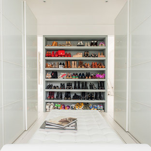 オックスフォードシャーの大きい女性用コンテンポラリースタイルのおしゃれなウォークインクローゼット (フラットパネル扉のキャビネット、白いキャビネット、白い床) の写真