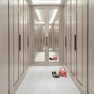 Ispirazione per una cabina armadio per donna design con ante con riquadro incassato, ante beige e pavimento bianco