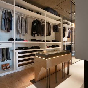 Inspiration för industriella walk-in-closets för män, med öppna hyllor, vita skåp, mellanmörkt trägolv och brunt golv