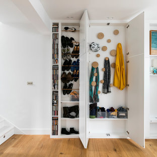 Inspiration pour un placard dressing design neutre avec des portes de placard blanches et un sol en bois brun.