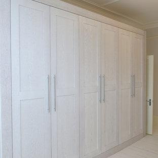 Modelo de vestidor unisex, contemporáneo, grande, con armarios estilo shaker, puertas de armario de madera clara, suelo de madera pintada y suelo blanco
