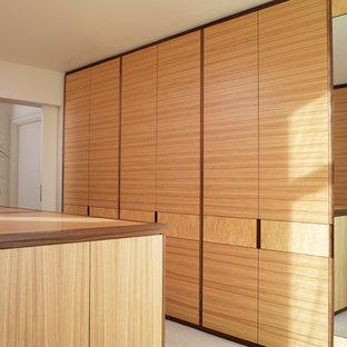 Modelo de armario vestidor unisex, moderno, grande, con armarios con paneles lisos, puertas de armario de madera oscura y moqueta