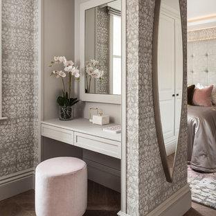 Foto de armario y vestidor de mujer, clásico renovado, de tamaño medio, con armarios con paneles empotrados, puertas de armario grises, suelo de madera en tonos medios y suelo marrón
