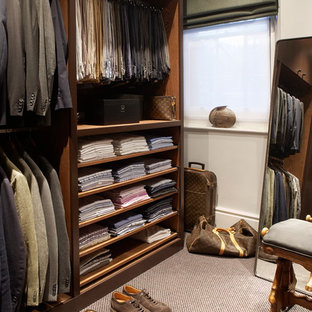 Large traditional walk-in wardrobe for men in London with open cabinets, dark wood cabinets, carpet and brown floors.