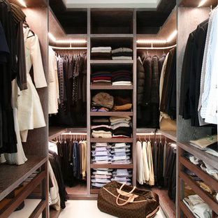 Trendy closet photo in London with open cabinets and dark wood cabinets