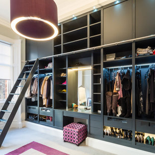 Photo of a contemporary dressing room for women in Glasgow with open cabinets, black cabinets, carpet and beige floors.