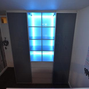 Esempio di un grande armadio o armadio a muro unisex minimalista con ante di vetro e ante grigie