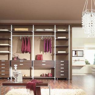 Diseño de armario vestidor unisex, contemporáneo, grande, con armarios abiertos, puertas de armario marrones y suelo de madera oscura