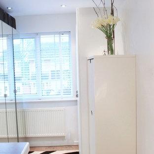 Foto di una cabina armadio unisex minimal di medie dimensioni con pavimento in compensato, ante lisce e ante bianche