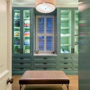 ロンドンの広い男女兼用トランジショナルスタイルのおしゃれなフィッティングルーム (ガラス扉のキャビネット、緑のキャビネット、淡色無垢フローリング、ベージュの床) の写真