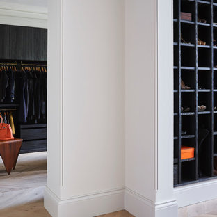 Large contemporary walk-in wardrobe in London with flat-panel cabinets, black cabinets and light hardwood flooring.