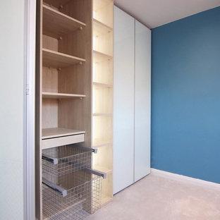 Esempio di un grande armadio o armadio a muro unisex con ante di vetro e ante in legno chiaro