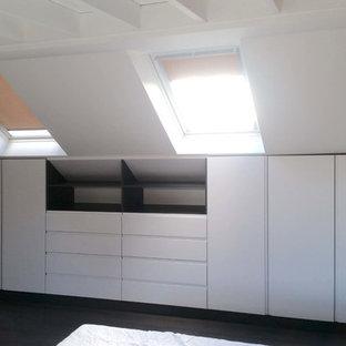 Foto de armario y vestidor moderno, de tamaño medio, con puertas de armario blancas, suelo laminado y suelo negro