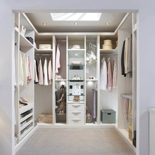 This is an example of a medium sized contemporary gender neutral walk-in wardrobe in London with open cabinets, light wood cabinets, carpet and beige floors.