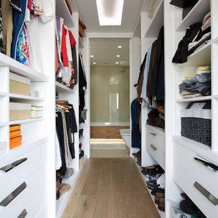 Foto de armario vestidor actual, de tamaño medio, con armarios abiertos, puertas de armario blancas y suelo de madera en tonos medios